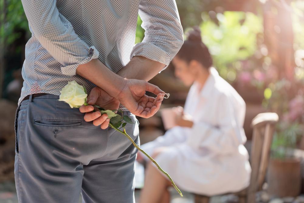 Mies kosimassa naista kihlasormuksella